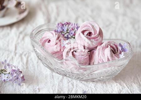 Zephyr casero dulce violeta o Marshmallow de grosella negra con flores lilas en jarrón de cristal sobre tela blanca de mesa