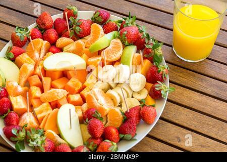 plato con surtido de rodajas de fruta sobre una mesa de madera y cristal con jugo de naranja fresco concepto de alimentación saludable Foto de stock