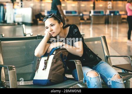 Molesta o aburrida chica turística o estudiante en el aeropuerto. Su vuelo se retrasó o estaba cansada.