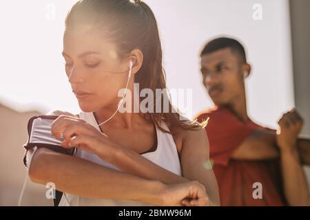 Primer plano de una mujer escuchando música con auriculares desde su smartphone mientras hace ejercicio en la ciudad con un hombre de fondo. Mujer usando un smarpp