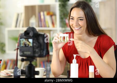 Feliz belleza influencer mujer mostrando productos cosméticos registra vídeo en la cámara sentado en casa