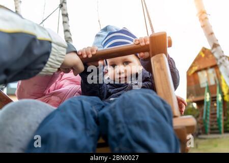 Dos adorables juguetones hermanos caucásicos niño niña disfrutar de divertirse girando columpio de madera en el patio trasero junto con el padre. Niño pequeño