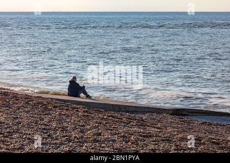 Una mujer se sienta en un resbaladizo en la playa de guijarros de Hampton, Herne Bay, y mira al mar, pensativamente, Reino Unido