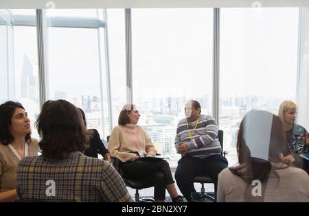 Gente de negocios hablando en círculo en la sala de reuniones