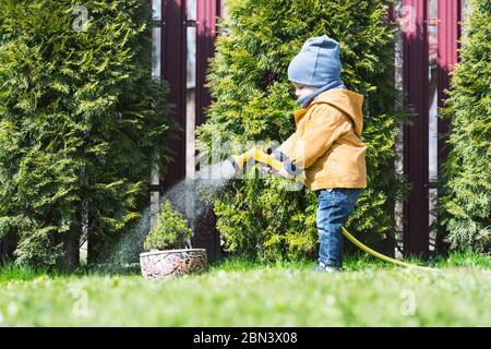 Un niño pequeño con riego puede regar árboles en el patio trasero. Concepto de la niñez feliz