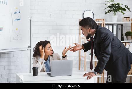 Compañeros de trabajo afroamericanos discutiendo entre sí en el cargo