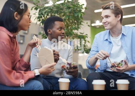 Grupo multiétnico de jóvenes comiendo comida para llevar y sonriendo durante el descanso de almuerzo en la escuela u oficina