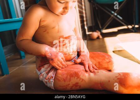 La niña creativa pinta en el suelo con la pintura de los niños un dibujo abstracto de los bebés sin formas.