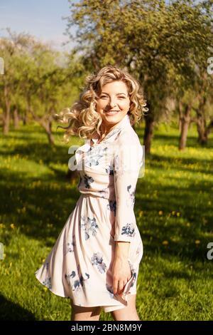 Feliz joven mujer con pelo rubio, vestido, posando al aire libre en un jardín con cerezos al sol, sonriendo. Rizos que revolotean en el viento