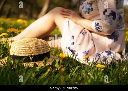 Mujer con un sombrero de paja en un campo de flores y hierba verde. Verano en el país. Céntrese en el sombrero
