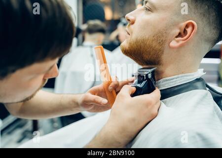 Barbería de corte barbudo hombre con máquina de afeitar en la peluquería. Proceso de peluquería. Primer plano de un estilista cortando la barba de un varón barbudo.
