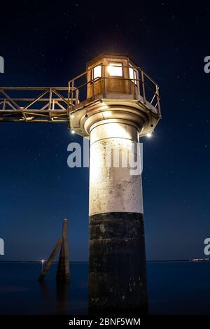 Tiro vertical de ángulo bajo de un faro capturado por el océano bajo el cielo estrellado Foto de stock