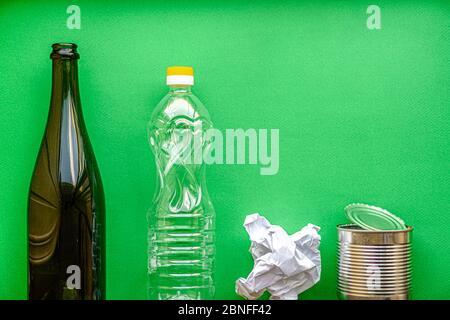 concepto de separación de basura, ecología, basura - disposición de la clasificación de residuos en 4 tipos: vidrio, plástico, papel, metal en un espacio de copia de fondo verde.