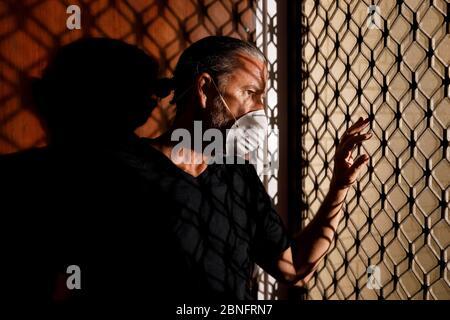 coronavirus masculino máscara médica cuarentena, concepto de auto aislamiento, frustrado hombre de mediana edad usando máscara protectora en casa mirando por la puerta principal