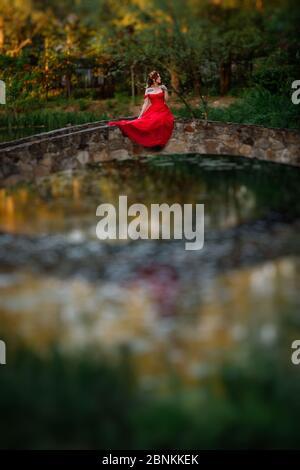 Pelirroja mujer tatuada con vestido rojo sentado en el puente de piedra Foto de stock