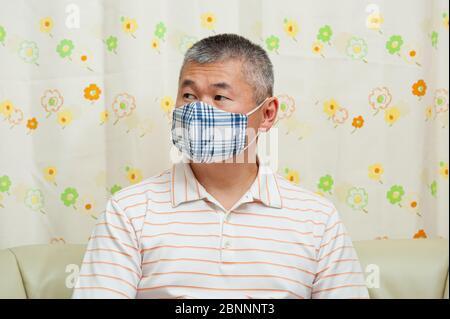 Retrato de un hombre asiático de mediana edad con máscara facial de tela DIY para proteger contra el coronavirus (COVID-19) y otras enfermedades infecciosas.