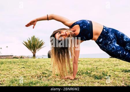 Concepto. De deporte y ejercicios de pérdida de peso - joven mujer caucásica gente haciendo pitas al aire libre en la naturaleza verde. Hierba sola - cuerpo perfecto y posición equilibrada