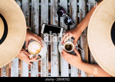 Por encima de la vista vetical de la pareja de mujeres caucásicos amigos juntos tomando café italiano y capuchino en el bar - concepto de amistad y estilo de vida alternativo lgbt - de madera de moda mesa al aire libre