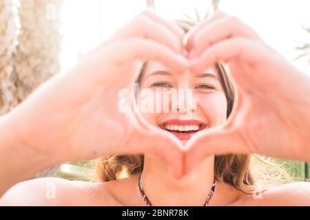 Retrato de cerca de hermosa. Mujer joven caucásica haciendo amor signo de corazón con las manos en la cámara - sol brillante fondo y felicidad alegre gente concepto