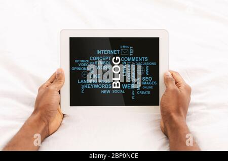 Primer plano de un hombre afroamericano sosteniendo un ordenador de tableta con palabras relacionadas con blogs en la pantalla, collage