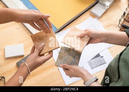 Manos de dos jóvenes diseñadoras comparando muestras de baldosas de mármol, mientras que la elección más apropiada para la nueva casa