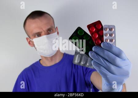 el médico lleva una máscara protectora sobre fondo azul. sostiene cápsulas en envases de blíster sobre una mano estirada en un guante. Enfoque selectivo Foto de stock