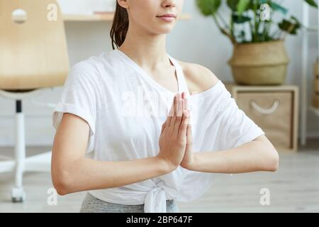 Retrato recortado de una joven contemporánea haciendo yoga en casa mientras se sienta en la posición de loto, copiar espacio