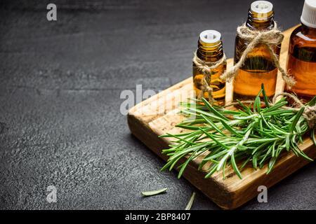 Ramas de hierbas de romero y botellas de aceite esencial de romero sobre fondo de piedra negra. Concepto de aromaterapia a base de hierbas.