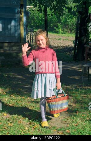 La chica del pueblo con un peinado desaliñado saluda y sostiene una cesta de manzanas en sus manos Foto de stock