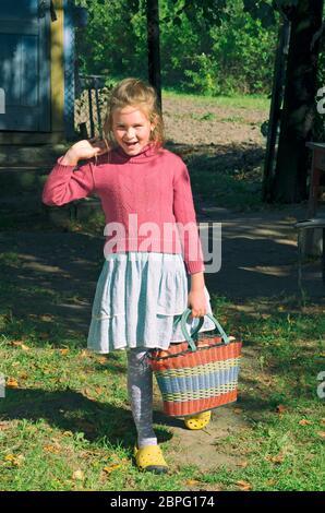La pequeña niña del pueblo sonríe y sostiene una cesta de manzanas de jardín en su mano Foto de stock