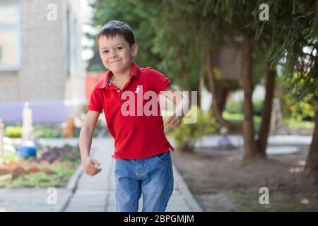 Bielorrusia, la ciudad de Goml, 26 de abril de 2019. Fotosesión en kindergarten.Funny niño preescolar está caminando por la calle. Niño alegre de seis años