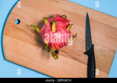 Pitaya madura y un cuchillo en una tabla de cortar. Corta la pitaya a la mitad. Fruta de dragón de verano. Vista superior de un diseño plano.