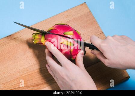 Primer plano de las manos de una mujer cortando una fruta madura de pitaya con un cuchillo en una tabla de madera. Pattaya está cortado en dos partes. La vista desde arriba.