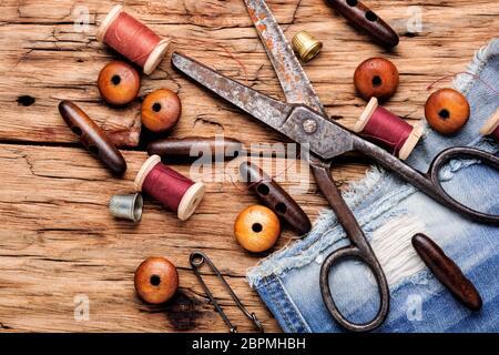 Carretes de hilo y herramientas básicas de costura sobre mesa de madera.kit de costura