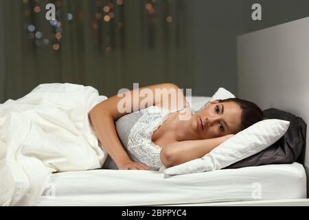 Insomniac mujer no puede dormir acostada en la cama en la noche en su domicilio.