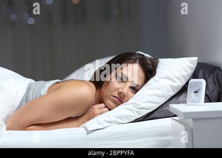Restless chica sufre insomnio mira en la cama en la noche