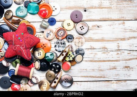 Carretes de hilos y botones en la mesa de madera