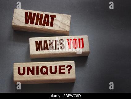 ¿Qué hace que el yiu único - frase sobre bloques de madera. Negocio o concepto de éxito de los cuidadores
