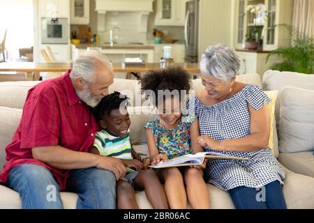 Pareja de carreras mixtas de alto rango sentada en el sofá con su nieto y nieta