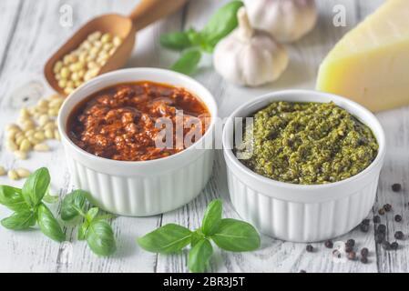Cuencos de clásico y pesto de tomates secados al sol con ingredientes sobre el fondo blanco de madera