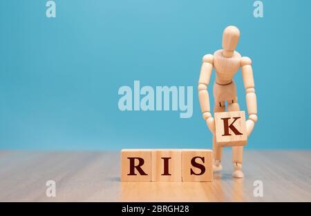 Marionetas de madera de pie y sosteniendo un cubo de madera con palabra de riesgo. Concepto de evaluación y análisis de crisis de negocio y control de inversiones en riesgo