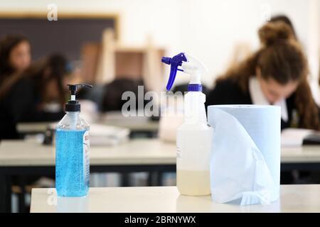 Deliberadamente borroso estudiantes en el fondo trabajando en el trabajo de clase. Desinfectante para manos bomba desinfectante con botella desinfectante en primer plano.