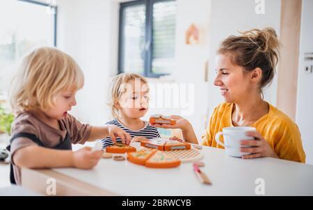 Madre con dos niños pequeños en el interior en el dormitorio jugando con juguetes.