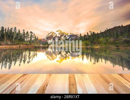 Cubierta de madera vacía mesa de la cubierta preparada para el montaje de la exhibición del producto con la montaña cuando el fondo de la puesta de sol.