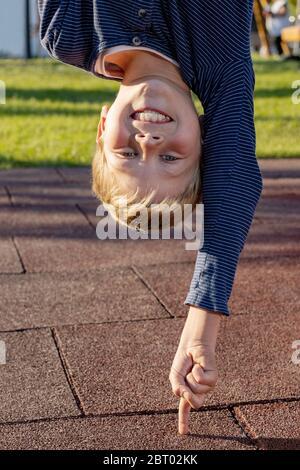 Niño boca abajo apoyado en un dedo fuera en el parque. Concepto para jóvenes que hacen las cosas fácilmente