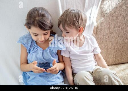 Los niños tienen un buen concepto de tiempo en casa. Cerrar hermano y hermana jugando con la tableta. Niños sentados en el sofá, jugando con la tableta. Los niños juegan un