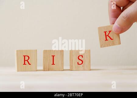 """La palabra """"riesgo"""" en el cubo de madera con la mano sosteniendo la letra K."""