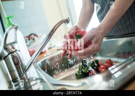 Las manos femeninas lavan la pimienta roja bajo un chorro de agua, contra el fondo de verduras en el fregadero. Cocinar alimentos.