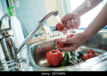 Las manos femeninas lavan los tomates rojos bajo un chorro de agua, contra el fondo de las verduras en el fregadero. Cocinar alimentos.