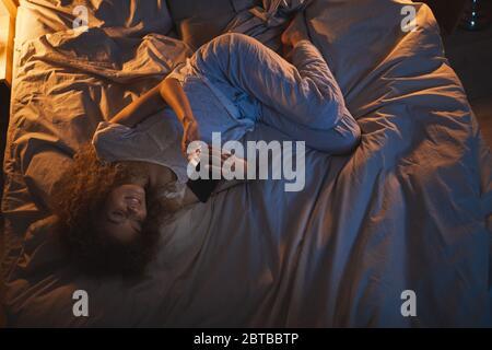 Vista de arriba abajo de la joven tumbada en la cama por la noche y usando el smartphone mientras que le da mensajes de texto novio, espacio de copia Foto de stock